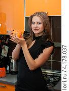 Купить «Красивая девушка с апельсином в руках стоит на кухне», эксклюзивное фото № 4178037, снято 5 января 2013 г. (c) Игорь Низов / Фотобанк Лори