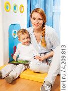 Купить «Мама с сыном сидят в детской комнате на полу. Мальчик играет в игру на планшетном компьютере», фото № 4209813, снято 24 декабря 2012 г. (c) Сергей Новиков / Фотобанк Лори