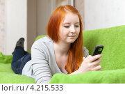 Молодая рыжеволосая девушка с телефоном лежит на диване. Стоковое фото, фотограф Яков Филимонов / Фотобанк Лори