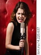 Купить «Экспрессивная певица на красном фоне», фото № 4220637, снято 25 декабря 2012 г. (c) Дмитрий Черевко / Фотобанк Лори