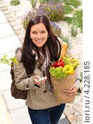 Улыбающаяся девушка с продуктами и сотовым телефоном. Стоковое фото, фотограф CandyBox Images / Фотобанк Лори