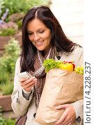Улыбающаяся девушка с продуктами читает смс. Стоковое фото, фотограф CandyBox Images / Фотобанк Лори