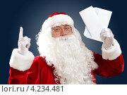 Купить «Дед Мороз с новогодним письмом в руках на темном фоне показывает вверх», фото № 4234481, снято 28 сентября 2012 г. (c) Sergey Nivens / Фотобанк Лори