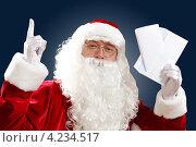 Купить «Дед Мороз с новогодним письмом в руках на темном фоне показывает вверх», фото № 4234517, снято 28 сентября 2012 г. (c) Sergey Nivens / Фотобанк Лори