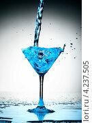 Купить «Струйка голубой жидкости льется в бокал», фото № 4237505, снято 11 декабря 2008 г. (c) Иван Михайлов / Фотобанк Лори