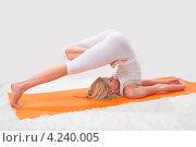Купить «Девушка выполняет упражнение йоги, закинув ноги за голову», фото № 4240005, снято 29 ноября 2011 г. (c) Николай Кокарев / Фотобанк Лори