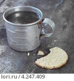 Купить «Металлическая кружка с водой и надломанный крекер», фото № 4247409, снято 26 июня 2019 г. (c) Food And Drink Photos / Фотобанк Лори