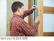 Купить «Мужчина меняет замок в двери», фото № 4253309, снято 16 декабря 2012 г. (c) Дмитрий Калиновский / Фотобанк Лори