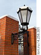 Купить «Красивый уличный фонарь в старинном стиле на заборе из красного кирпича», фото № 4258301, снято 20 января 2013 г. (c) Сергей Трофименко / Фотобанк Лори