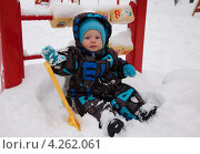 Ребенок с лопаткой сидит на снегу. Стоковое фото, фотограф Котова Мария / Фотобанк Лори