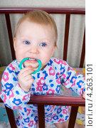 Купить «Маленький ребенок, девочка, стоит в кроватке и держит в зубах прорезыватель», фото № 4263101, снято 4 февраля 2013 г. (c) Попкова Ольга / Фотобанк Лори
