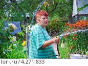 Купить «Женщина поливает огород из шланга», эксклюзивное фото № 4271833, снято 19 августа 2012 г. (c) Алёшина Оксана / Фотобанк Лори