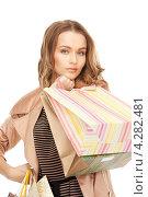 Купить «Очаровательная молодая женщина в бежевом плаще с пакетами покупок в руках», фото № 4282481, снято 10 октября 2010 г. (c) Syda Productions / Фотобанк Лори