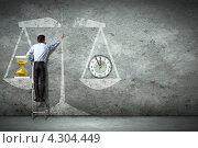 Мужчина в белой рубашке стоит на приставной лестнице и рисует большие весы с песочными и механическими часами на чашах. Стоковое фото, фотограф Sergey Nivens / Фотобанк Лори