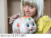 Девушка держит в руке 1 евро и свинью-копилку. Стоковое фото, фотограф Андрей Новосёлов / Фотобанк Лори