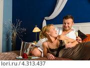 Влюбленная пара с шампанским на кровати. Стоковое фото, фотограф CandyBox Images / Фотобанк Лори