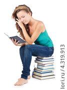 Купить «Студентка читает книгу, сидя на стопке книг», фото № 4319913, снято 22 августа 2012 г. (c) Elnur / Фотобанк Лори