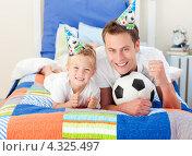 Купить «Папа и маленький сын болеют за футбол по телевизору на кровати», фото № 4325497, снято 18 октября 2009 г. (c) Wavebreak Media / Фотобанк Лори