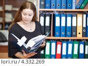 Купить «Молодая женщина с открытой папкой с документами стоит около шкафа», фото № 4332269, снято 16 февраля 2013 г. (c) Кекяляйнен Андрей / Фотобанк Лори