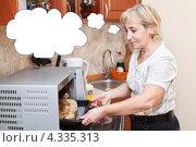 Купить «Пожилая домохозяйка достает из микроволновки курицу, запеченную в пакете», фото № 4335313, снято 2 октября 2011 г. (c) Кекяляйнен Андрей / Фотобанк Лори