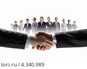 Купить «Мужчины пожимают друг другу руки, заключая сделку, на белом фоне с группой бизнесменов», фото № 4340989, снято 21 августа 2018 г. (c) Sergey Nivens / Фотобанк Лори