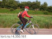 Купить «Женщина велосипедист едет на велосипеде по велосипедной дорожке на фоне природы», фото № 4350161, снято 31 августа 2011 г. (c) Ольга Липунова / Фотобанк Лори