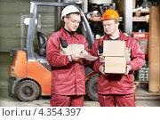 Купить «Двое складских рабочих на фоне погрузчика», фото № 4354397, снято 11 февраля 2013 г. (c) Дмитрий Калиновский / Фотобанк Лори