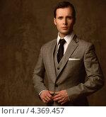 Купить «Успешный мужчина в классическом деловом костюме-тройке стоит на коричневом фоне», фото № 4369457, снято 10 февраля 2012 г. (c) Andrejs Pidjass / Фотобанк Лори