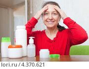 Пожилая женщина сидит за столом перед косметическими средствами и наносит крем на лицо. Стоковое фото, фотограф Яков Филимонов / Фотобанк Лори