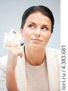 Купить «Красивая деловая женщина сидит за рабочим столом в офисе с деньгами в руках», фото № 4383681, снято 18 июня 2011 г. (c) Syda Productions / Фотобанк Лори