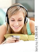 Купить «Счастливая девушка слушает в наушниках музыку из плеера», фото № 4389441, снято 27 марта 2010 г. (c) Wavebreak Media / Фотобанк Лори