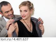 Купить «Мужчина помогает женщине одеться», фото № 4401637, снято 6 декабря 2010 г. (c) Phovoir Images / Фотобанк Лори