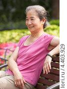 Пожилая китайская женщина на скамейке в парке. Стоковое фото, фотограф Monkey Business Images / Фотобанк Лори