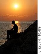 Мужчина сидит на скале на фоне заходящего солнца. Стоковое фото, фотограф Dmitry Burlakov / Фотобанк Лори
