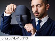 Купить «Молодой мужчина в костюме держит черную маску», фото № 4410913, снято 2 июля 2020 г. (c) Elnur / Фотобанк Лори