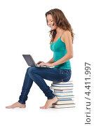 Купить «Студентка работает с ноутбуком сидя на стопке книг», фото № 4411997, снято 22 августа 2012 г. (c) Elnur / Фотобанк Лори