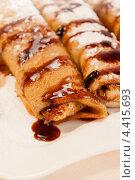 Купить «Десерт - блины с начинкой из орехов и шоколадным соусом», фото № 4415693, снято 24 февраля 2012 г. (c) ElenArt / Фотобанк Лори