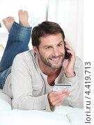 Улыбающийся мужчина с кредитной картой разговаривает по телефону дома. Стоковое фото, фотограф Phovoir Images / Фотобанк Лори