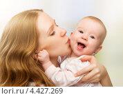 Купить «Счастливая мама целует маленького ребенка», фото № 4427269, снято 4 марта 2013 г. (c) Евгений Атаманенко / Фотобанк Лори