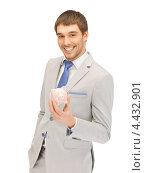 Купить «Счастливый бизнесмен в сером костюме с копилкой в руках», фото № 4432901, снято 8 апреля 2012 г. (c) Syda Productions / Фотобанк Лори