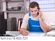 Рабочий разговаривает по телефону в мастерской. Стоковое фото, фотограф Phovoir Images / Фотобанк Лори