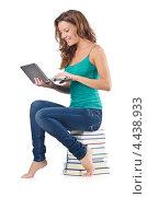 Купить «Студентка сидит на стопке книг с ноутбуком», фото № 4438933, снято 22 августа 2012 г. (c) Elnur / Фотобанк Лори