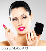 Купить «Красивая молодая женщина красит губы на светлом фоне», фото № 4453473, снято 19 марта 2013 г. (c) Валуа Виталий / Фотобанк Лори