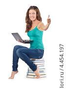 Купить «Студентка с нетбуком сидит на стопке книг», фото № 4454197, снято 22 августа 2012 г. (c) Elnur / Фотобанк Лори
