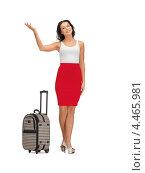 Красивая брюнетка в обтягивающей красной юбке с чемоданом на колесиках на белом фоне. Стоковое фото, фотограф Syda Productions / Фотобанк Лори
