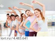 Наклоны в стороны. Молодые люди занимаются фитнесом в зале спортклуба. Стоковое фото, фотограф Raev Denis / Фотобанк Лори