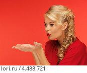 Купить «Красивая молодая блондинка в красном платье сдувает дыханием что-то с ладоней», фото № 4488721, снято 7 октября 2012 г. (c) Syda Productions / Фотобанк Лори