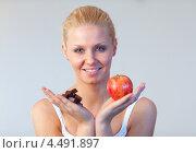 Купить «Блондинка держит в руке кусочки шоколадной плитки и красное яблоко», фото № 4491897, снято 16 августа 2009 г. (c) Wavebreak Media / Фотобанк Лори