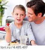 Купить «Радостная девочка ест ягоды, сидя на коленях у папы», фото № 4495497, снято 14 декабря 2018 г. (c) Wavebreak Media / Фотобанк Лори