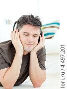 Купить «Молодой человек слушает музыку в наушниках», фото № 4497201, снято 16 мая 2010 г. (c) Wavebreak Media / Фотобанк Лори